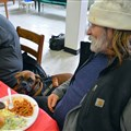 David dines with his dog at Magnolia Avenue United Methodist Church on Monday, Dec. 10. Milo the service dog was later treated with a bowl of meatballs.