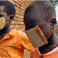 In Ugandan refugee camps, South Sudanese children wear homemade cardboard masks to fend off COVID-19. (Photo from Leviticus Pictures TV.)