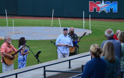 The pastor and praise team of First United Methodist Church lead worship in Calfee Park, home of the Pulaski Yankees.